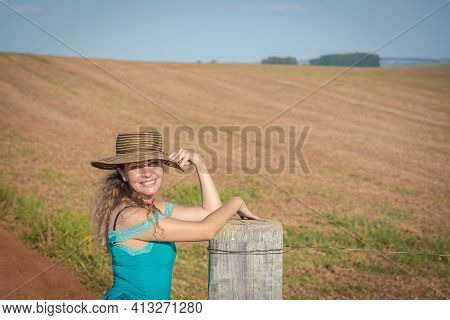 Brazilian Woman Wearing A Hat Propped Up On A Rural Property Fence