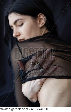 European White Girl With Dark Hair Isolated On Black With Hand Under Transparent Top