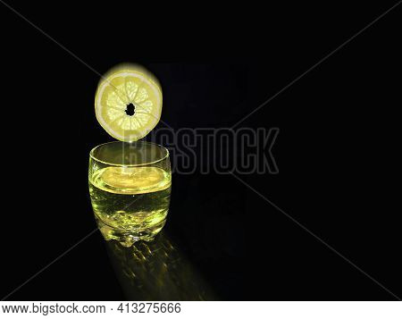 Lemon Circle Falling Into Clear Glass With Alcoholic,non-alcoholic Drink,lemon Juice.quenching Thirs