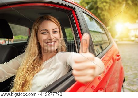 Happy Beautiful Woman Is Driving A Red Car.