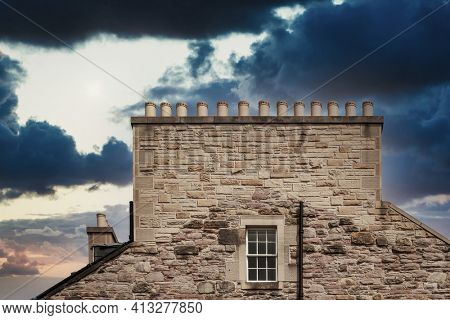 Element of the facade of house and the roof with chimney on dramatic sky
