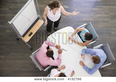Four Businesspeople At Boardroom Table Watching Presentation