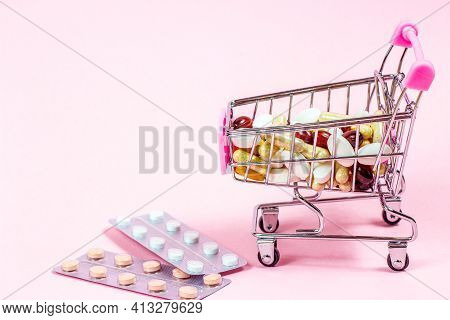Shopping Cart With Different Medical Pills And Capsules In It On Pink Background. Pharmacology And D