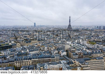 View on Eiffel tower over the roofs of Paris on a grey cloudy day