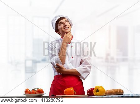 Young Male Chef Standing With Folded Arms And Looking Up Dreamily. Pensive Culinary School Student I