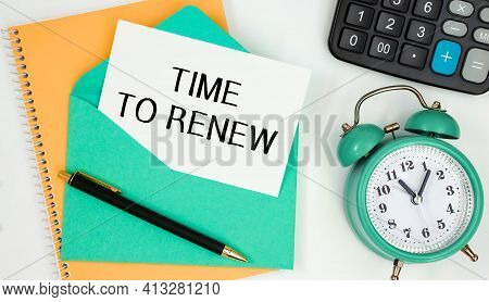 Card On A Postal Envelope With The Text Time To Renew, Clock, Calculator, Pen.
