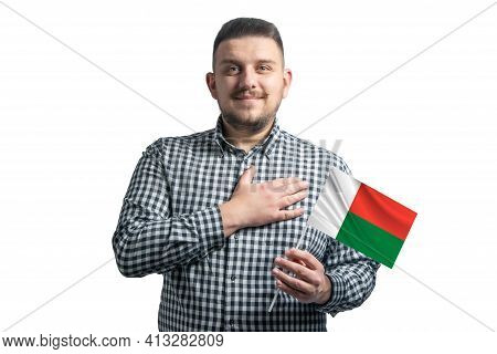 White Guy Holding A Flag Of Madagascar And Holds His Hand On His Heart Isolated On A White Backgroun