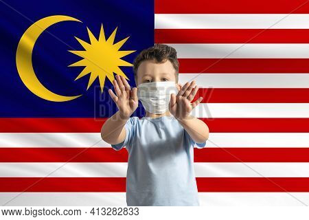 Little White Boy In A Protective Mask On The Background Of The Flag Of Malaysia. Makes A Stop Sign W