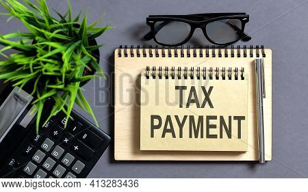 Blank Note Pad With Tax Payment Text On The Grey Wooden Background