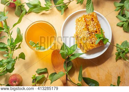 A Yellow Carbonated Drink Poured Into Two Glasses Stands On A Wooden Table Among Mint Leaves And Nex