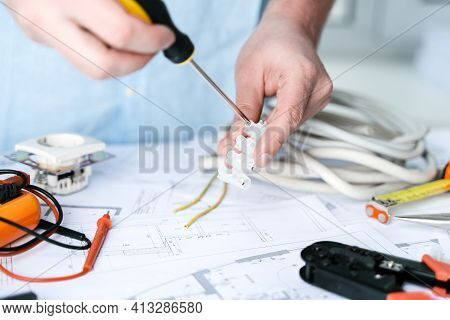 Man Repairer Making Electricity Project In House.repairs Planning.drawing,diagrams,plan Of Electrifi