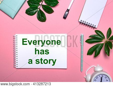 Everyone Has A Story Is Written In Green On A White Notepad On A Pink Background Surrounded By Notep