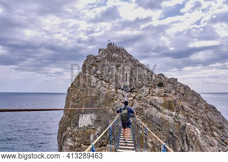 A Man With A Backpack Walks Over A Suspension Bridge To Diva Rock, Black Sea Coast, Near Yalta, Crim