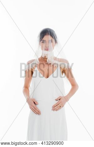 Young, Pregnant Bride In Veil Touching Tummy Isolated On White.