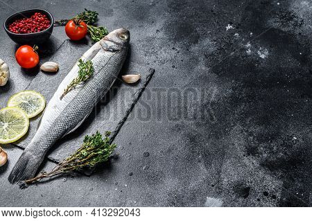 Seabass Fish With Herbs And Lemon, Raw Sea Bass. Black Background. Top View. Copy Space