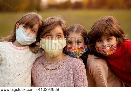Group Of Four School-age Girlfriends Wearing Protective Masks Await End Of Pandemic Lockdown, Freedo
