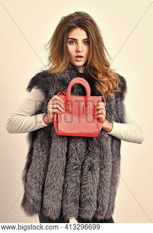 Fashion And Shopping Concept. Female Stylish Fashion Model. Woman In Fur Coat With Handbag On White