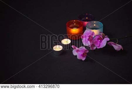 Purple Orchid And  Candles On Dark Background. View With Copy Space.