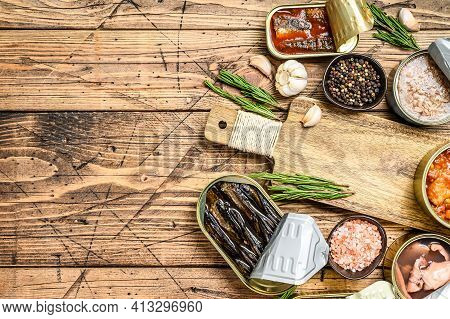 Opened Cans Conserve With Saury, Salmon, Sprats, Sardines, Squid And Tuna. Wooden Background. Top Vi
