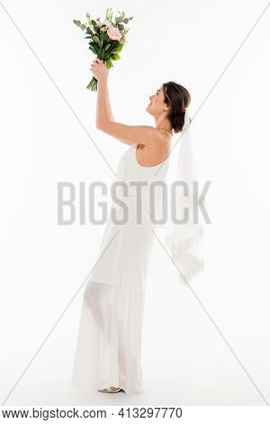 Side View Of Fiancee Holding Wedding Bouquet In Raised Hands On White.