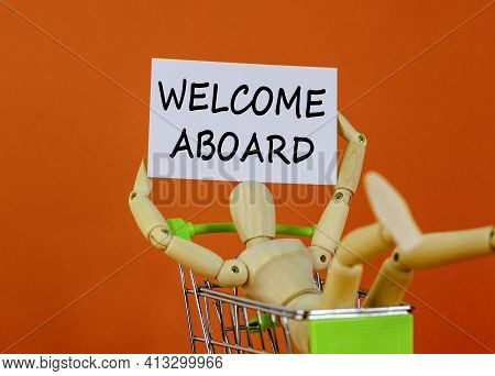 Welcome Aboard Symbol. White Paper. Words 'welcome Aboard'. Wooden Model Of A Human In A Shopping Ca