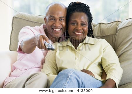 Couples Relaxing In Living Room Holding Remote Control And Smiling