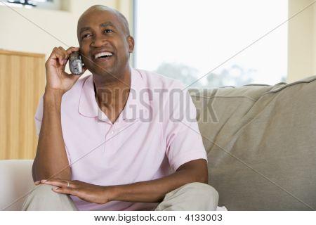 Man zit In levende kamer met behulp van telefoon- en glimlachen