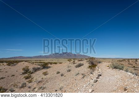 Deserted Path In The New Mexico Desert With An Expansive View Of Mountain Ridges Under Deep Blue Sky