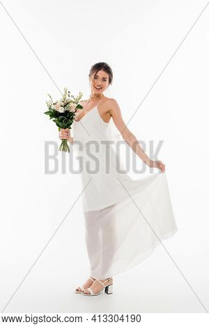 Full Length View Of Happy Fiancee With Wedding Bouquet Smiling At Camera On White.