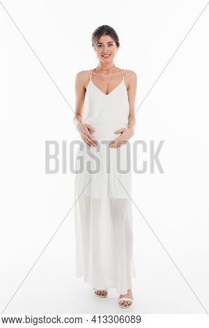 Full Length View Of Happy, Pregnant Fiancee Touching Belly While Smiling At Camera On White.