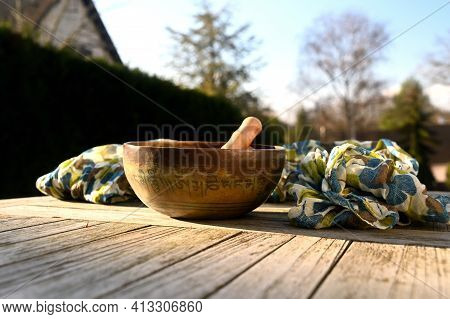 Tibetan Singing Bowl On A Table Outdoor. Tibetan Singing Bowl On A Table Outdoor. English Translatio