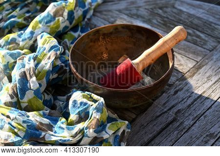 Tibetan Singing Bowl On A Table Outdoor. English Translation Of Mantras : Transform Your Impure Body