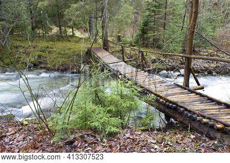 Homemade Wooden Pedestrian Bridge Over A Fast Mountain River In A Deep Forest. River Stiavnica. Jans