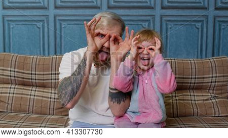 Father And Girl Daughter Kid In Pajamas Fooling Sit On Couch In Living Room Smile Look At Camera Sho