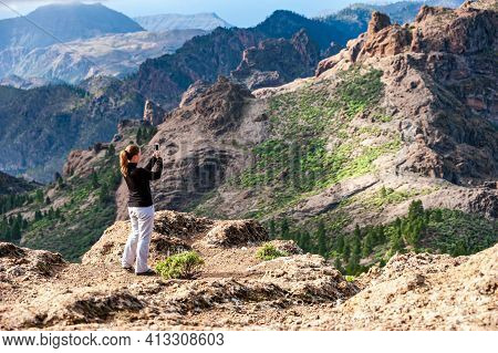 Young Woman Hiker From Behind Taking Picture Of Volcanic Landscape With Mobile Phone. Female Trekker