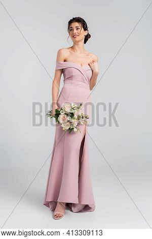 Full Length View Of Elegant Fiancee Looking Away While Holding Wedding Bouquet On Grey.