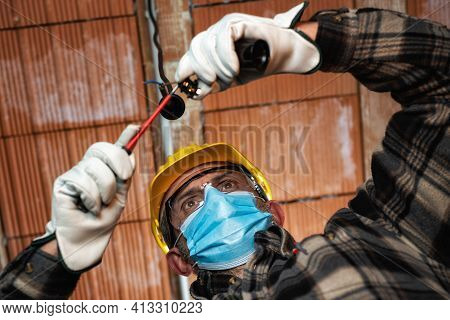 Electrician Worker At Work Replaces The Lamp Holder Protected By Helmet, Safety Goggles And Gloves;