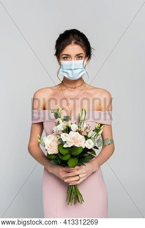 Young Fiancee In Medical Mask Holding Wedding Bouquet Isolated On Grey.