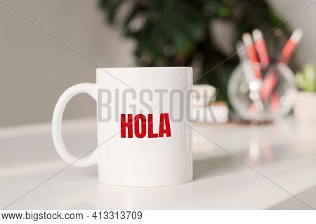 Hola Sign In Spanish Language On The Mug On Business Table
