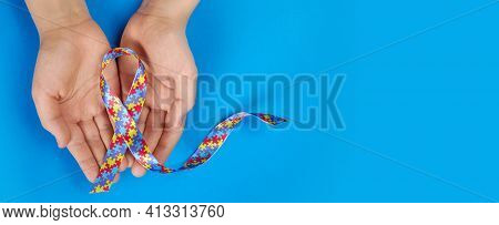 World Autism Awareness Day. Autistic Boy Hands Holding Puzzle Pattern Ribbon On Blue Background