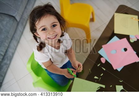 Adorable Child Holding Scissors, Cutting Color Paper And Cute Smiles To The Camera. Creative Hobby.