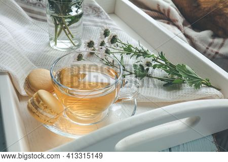 Cup Of Tea, Books, Chrysanthemum Flowers And Macaroons In Tray On The Table. Cozy Home Concept. Colo
