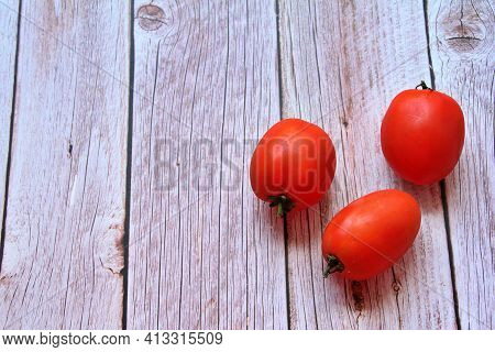 Three Oblong Tomatoes, Long Tomatoes Arranged On A Light Wooden Background, Red Vegetables