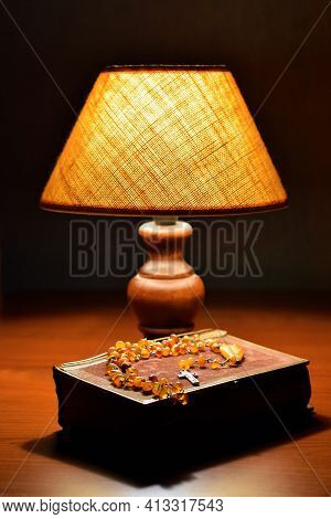 Soft Light Of Table Lamp, Old Book (prayer Book Or Bible) And Amber Catholic Rosary On Table. Religi