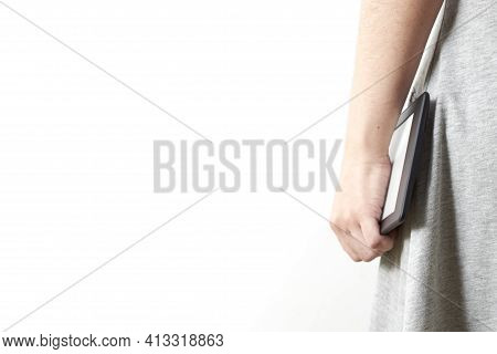 Unrecognizable Young Woman In A Gray Dress Holding An Electronic Reader. Image With White Background