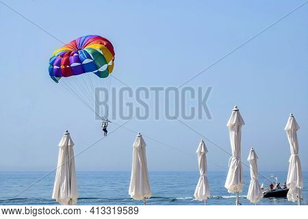 Multi-colored Parachute With A Man On The Background Of The Sea And White Closed Beach Umbrellas. Th