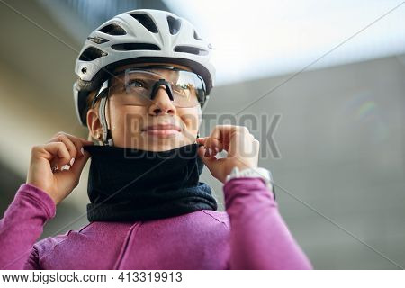 Portrait Of Professional Female Cyclist Wearing Pink Suit And Neck Warmer Smiling Away While Getting