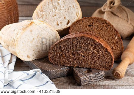 Rye Bread And White Wheat Bread On Cutting Board. Whole Grain Rye Bread With Seeds On Rustic Backgro