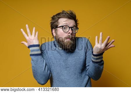 The Strange, Surprised Man Shrugs His Shoulders And Makes A Bewildered Hand Gesture. Yellow Backgrou