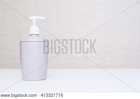 A Gray Liquid Soap Dispencer, Bottle Against White Background In A Bathroom With Copy Space
